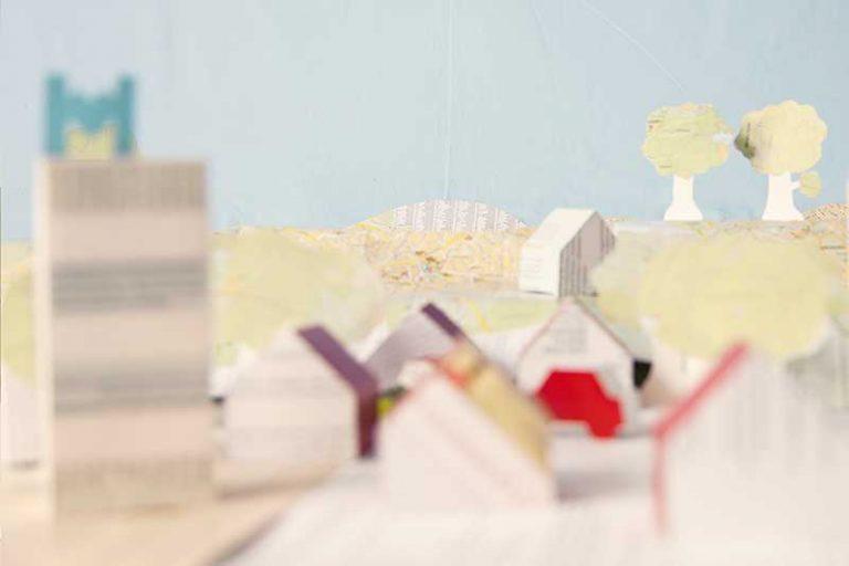 Landskap bestående av hus och träd, skapat genom att klippa och klistra ihop papper.