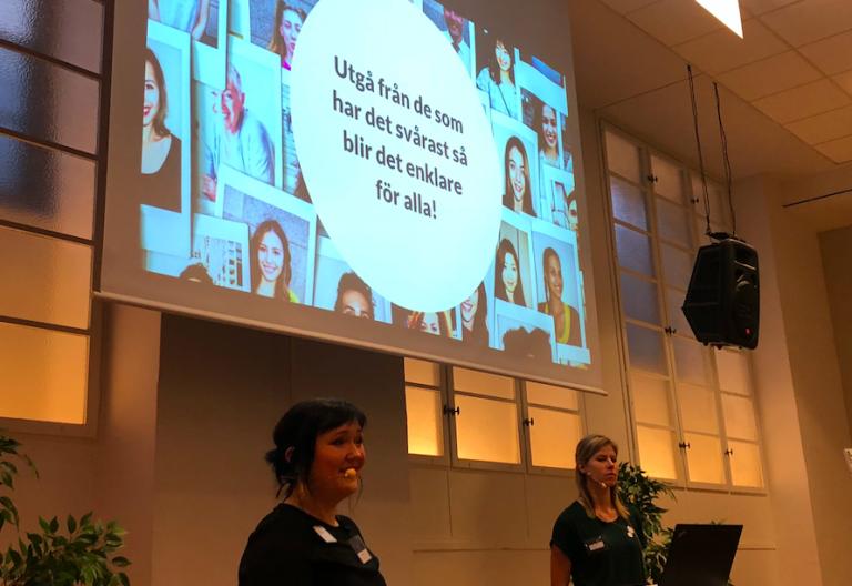 """Moa och Frida presenterar, framför skärm med texten """"Utgå från de som har det svårast, så blir det enklare för alla!""""."""