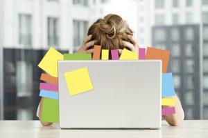 En stressad kvinna som uppgivet lutar huvudet i händerna framför en överbelamrad dator.