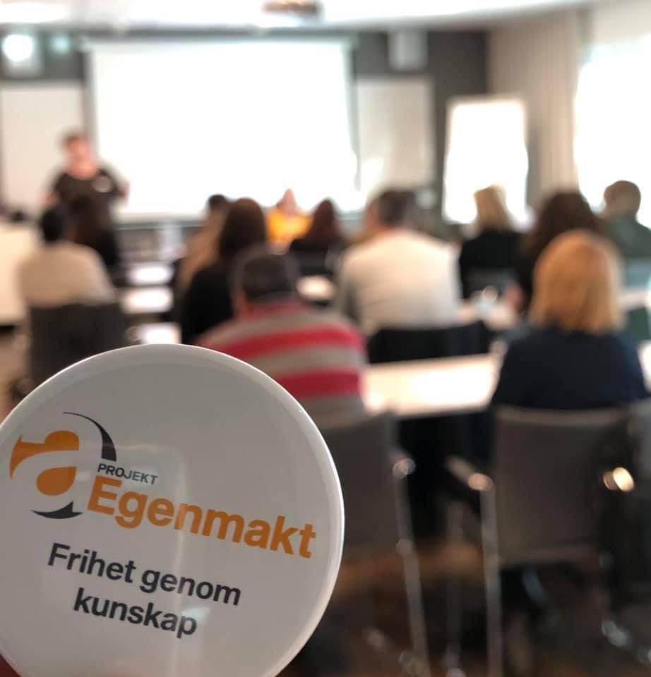 """Foto, i förgrunden märke med texten """"Projekt Egenmakt, Frihet genom kunskap"""", i bakgrunden människor i möteslokal."""