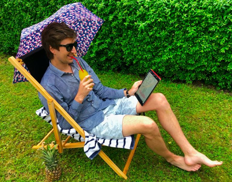 Foto på Peter från Xtractor, i solstol hållandes i iPad, med regnig bakgrund.