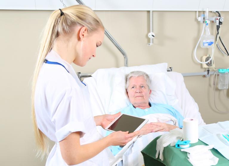 Äldre patient i sjukhussäng med läkare eller sjuksköterska bredvid.