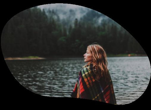 Kvinna med filt över axlarna tittar ut över en skogssjö.